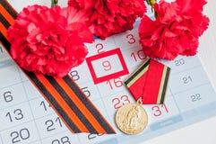 9 Mei - rode anjer met George van oorlogsmedailles lint die op de kalender met 9 Mei-datum liggen Stock Foto