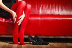 Meia-calça vermelha dos pés da mulher da forma no sofá fotografia de stock royalty free
