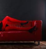 Meia-calça vermelha dos pés da mulher da forma no sofá Fotografia de Stock