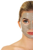 Meia cara da jovem mulher com máscara facial Imagens de Stock
