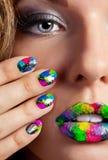 Menina com os pregos multicoloridos bonitos e a composição da sirigaita Fotos de Stock Royalty Free