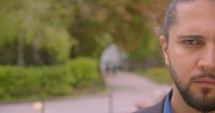 Meia cara do close-up disparada do indivíduo considerável do moderno que olha agressivelmente na câmera no parque video estoque