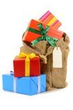 A meia do Natal ou o saco de Santa encheram-se com os presentes isolados no fundo branco Imagens de Stock