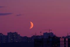 Meia lua acima dos edifícios da cidade na noite Fotos de Stock Royalty Free