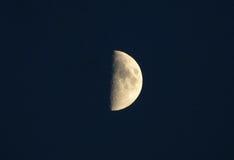 Meia lua em um céu escuro com detalhes de crateras Fotos de Stock Royalty Free