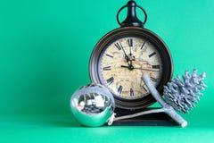 Meia-noite, quinquilharia e cone do pulso de disparo de ano novo no ramo de árvore do abeto do pinho Fundo verde Papai Noel em um fotografia de stock royalty free