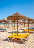 Meia Praia beach in Lagos, Algarve, Portugal. Yellow and blue sun beds on Meia Praia beach in Lagos, Algarve, Portugal Stock Photo