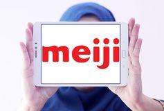 Meiji Holdings logo. Logo of Meiji Holdings company on samsung tablet holded by arab muslim woman . the Meiji Group offers a wide range of products including Stock Image