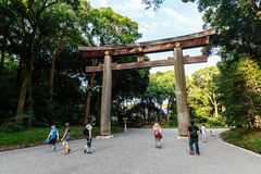 Meiji Shrine shrine. Tourists walking under the Torii at the entrance to the Meiji Shrine shrine in Shibuya, Tokyo, Japan Royalty Free Stock Photography