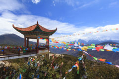 Meili snow mountain with Prayer flags and Chinese style roof, Yunnan, China Stock Photo
