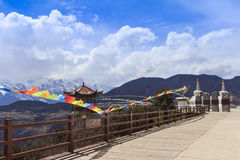 Meili snow mountain with Prayer flags and Chinese style roof, Yunnan, China Stock Images