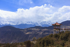 Meili snow mountain with Prayer flags and Chinese style roof, Yunnan, China Royalty Free Stock Photos