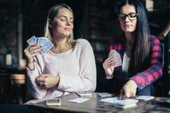 Meilleurs amies jouant la carte de jeu à la maison Image stock