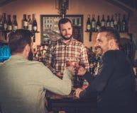 Meilleurs amis ayant l'amusement et buvant de la bière pression au compteur de barre dans le bar Images libres de droits