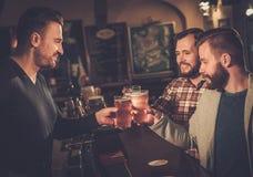 Meilleurs amis ayant l'amusement et buvant de la bière pression au compteur de barre dans le bar Photos libres de droits