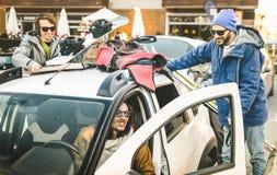 Meilleurs amis ayant l'amusement préparant ensemble la voiture pour le ski et le surf des neiges Photos libres de droits