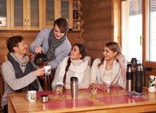 Meilleurs amis buvant du thé chaud dans la cuisine confortable au cottage d'hiver Photo stock