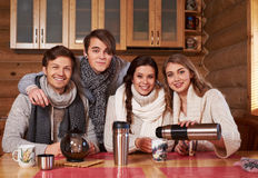 Meilleurs amis buvant du thé chaud dans la cuisine confortable au cottage d'hiver Image libre de droits