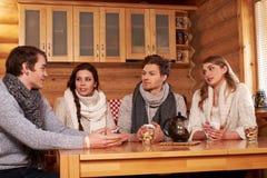 Meilleurs amis buvant du thé chaud dans la cuisine confortable au cottage d'hiver Photos stock