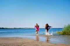 Meilleurs amis courant pour nager en rivière Photographie stock