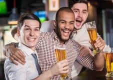Meilleurs amis dans une barre Les hommes crient et se réjouissent dans la réunion et le drin Photo libre de droits