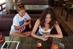 Meilleurs amis de femmes à l'aide des téléphones de cellules tout en se reposant dans le café, comprimé numérique avec l'écran de Images stock