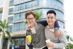 Meilleurs amis Deux types étreignant et marchant dans la ville Image stock