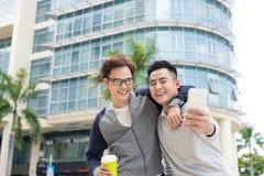 Meilleurs amis Deux types étreignant et marchant dans la ville Photos stock