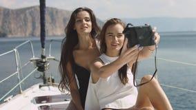 Meilleurs amis employant l'appareil-photo et prenant le selfie sur le selfie de luxe de bateau à voile Photographie stock libre de droits