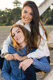 Meilleurs amis féminins s'asseyant sur les escaliers en bois Image libre de droits