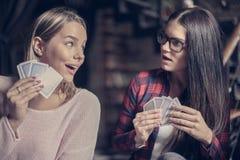 Meilleurs amis jouant la carte de jeu et se regardant Photo stock