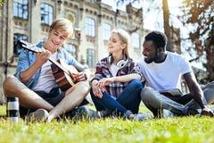 Meilleurs amis jouant la guitare tout en passant le temps dehors Photos stock