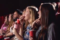 Meilleurs amis observant le film drôle au cinéma Photo libre de droits