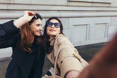 Meilleurs amis prenant un selfie dehors sur la rue Image libre de droits