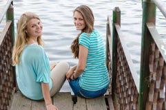 Meilleurs amis s'asseyant sur le pont par la rivière Image stock