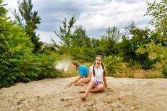 Meilleurs amis s'asseyant sur le sable à la plage Images stock
