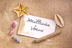 Meilleurs Voeux, written on a note in the sand with seashells Stock Images