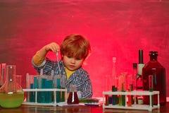 Mein Chemieexperiment Netter l?chelnder kleiner Junge, der Spa? gegen blaue Wand hat Mammamesswert mit Sohn Schulchemie stockbilder