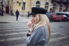 Meine Hände waren kalt Attraktives blondes Gehen um die Stadt, Mädchen in einem stilvollen Hut und einen grauen Mantel Stockbild