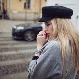Meine Hände waren kalt Attraktives blondes Gehen um die Stadt, Mädchen in einem stilvollen Hut und einen grauen Mantel Stockbilder