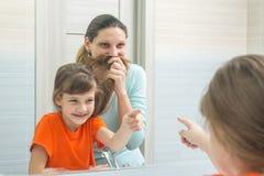 Meine Tochter und Mutter haben den Spaß, der meine Mutter betrachtet, die ihr Haar zu ihrem Gesicht wie einem Schnurrbart setzen Stockfotografie