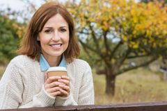 Meio atrativo feliz café bebendo envelhecido da mulher imagem de stock