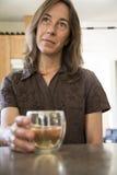 Meio atrativo mulher envelhecida no vinho bebendo da cozinha Fotos de Stock Royalty Free