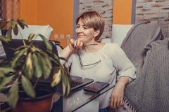 Meio bonito mulher envelhecida que usa seu portátil no conforto de sua sala de visitas fotografia de stock royalty free
