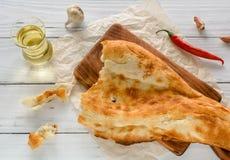 meio caucasian quebrado do pão do pão árabe, encontrando-se em uma placa de corte Fundo de madeira claro fotografia de stock