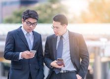 Meio comprimento do homem de negócios dois moderno farpado novo que usa o punho esperto do telefone que olha para baixo a tela -  fotografia de stock