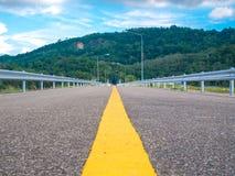 Meio da estrada asfaltada no fundo da represa com montanha e w Imagem de Stock