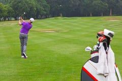 Meio do ar da bola do tiro do ferro do fairway do jogador de golfe fotografia de stock