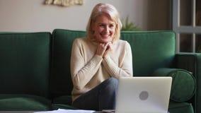 Meio entusiasmado vencedor envelhecido da sensação da mulher que olha o portátil video estoque