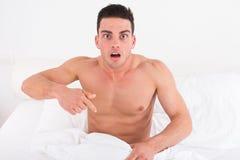 Meio homem novo despido na cama que olha para baixo em seu roupa interior em olá! Fotografia de Stock Royalty Free